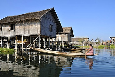 Woman in row boat in front of pile dwellings, Inle Lake, Burma, Myanmar, Southeast Asia