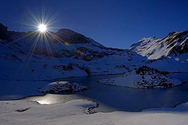 Snowy mountain lake in backlight, Hindelang, Allgaeu, Bavaria, Germany, Europe