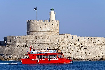 An excursion boat passes the harbor entrance, Rhodes town, Rhodes island, Greece, northern part, Aegean Sea, Southern Europe, Europe