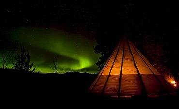 Illuminated teepee, tipi, tepee, Northern Lights, Polar Lights, Aurora Borealis, green, swirling, near Whitehorse, Yukon Territory, Canada