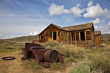 Rusty old car wreck in front of a dilapidated house, Bodie State Park, ghost town, mining town, Sierra Nevada Range, Mono County, California, USA