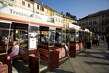 Orta San Giulio, Lago d'Orta, main square with little train for sight-seeing tours and waterfront antique palaces, Novara, Piedmont, Italy, Europe