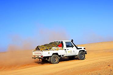 Jeep at high speed on a desert road, Sahara, Libya, Africa