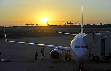 Qantas Airlines Boeing 717 refueling at sunrise, Brisbane International Airport, cranes in the rear, harbour, Brisbane, Queensland, Australia