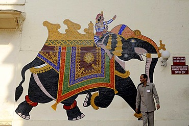 Indian in front of the mural of an elephant with a rider in the city palace, Udaipur, Rajasthan, North India, India, South Asia, Asia