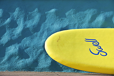 Yellow surfboard in front of a wall, Praa Sands, Cornwall, England, United Kingdom, Europe