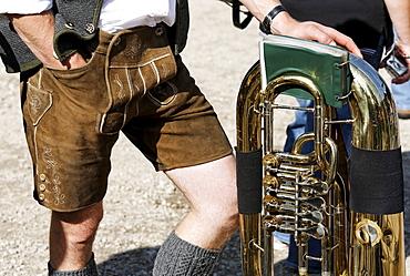 Man in traditional lederhosen leather pants leaning on a tuba, brass band, St. Wolfgang, Salzkammergut region, Upper Austria, Austria, Europe