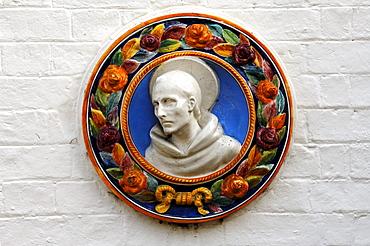 Ceramic figure of St. Francis on a community hall, High Street, Hemingford Gray, Cambridgeshire, England, United Kingdom, Europe