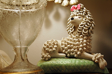 Porcelain poodle, lying on a green cushion, old hand-made porcelain figure from around 1940, Armscote, Warwickshire, England, United Kingdom, Europe