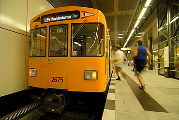 Two passengers running to the new subway line U55, with a traditional yellow subway carrriage, Brandenburger Tor Station, Berlin, Germany, Europe
