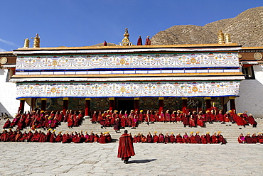 Tibetan monks wearing robes of the Gelug Order sitting on the stairs in front of the Assembly Hall, Tibetan Dukhang, the Labrang Monastery, Xiahe, Gansu, China, Asia