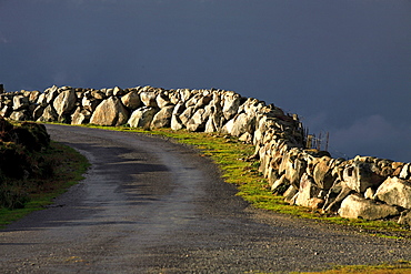 Sunlit stone wall fence and road with dark storm cloud, Republic of Ireland, Europe