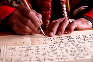 Priest writing ancient Dongba script, hands, Dongba Research Center at the Black Dragon Pool, Lijiang, UNESCO World Heritage Site, Yunnan Province, People's Republic of China, Asia