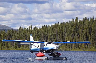 Taxiing de Havilland Canada DHC-3 Otter, Floatplane, Canoe tied to float, bush plane, Caribou Lakes, upper Liard River, Yukon Territory, Canada