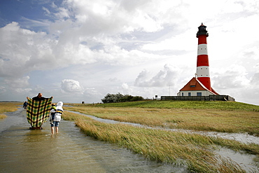 Tourists making a sail from a blanket in hurricane winds over the North Sea, path to Westerheversand Lighthouse, Schleswig-Holstein, Germany, Europe