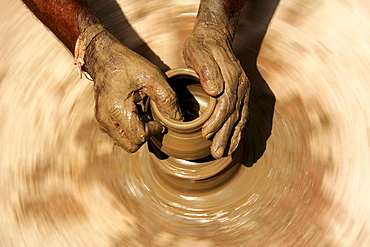 Hands of a potter, 58, in Dunjarpur, forming a piece of pottery on the potter's wheel, Rajasthan, India, Asia
