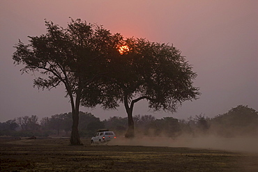 Sunset with all-terrain vehicle in the South Luangwa National Park, Zambia, Africa