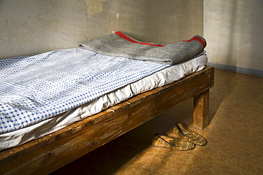 Cot with original bed covers, blanket and slippers, Berlin-Hohenschoenhausen memorial, former prison of the GDR's secret service, Berlin, Germany, Europe
