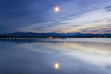 Full moon and its reflection in Lake Starnberg with the Bavarian Alps in the back, near Ambach, Bavaria, Germany, Europe