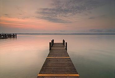 Sun rising over a pier in the calm Lake Starnberg, Bavaria, Germany, Europe