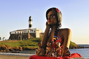 Traditional arts and crafts, clay figurine of a girl in love, namoradinha, and Forte de Santo Antonio da Barra fortress with Farol da Barra lighthouse, Salvador, Bahia, UNESCO World Heritage Site, Brazil, South America