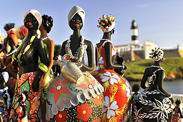 Traditional arts and crafts, clay figurines of women, and Forte de Santo Antonio da Barra fortress with Farol da Barra lighthouse, Salvador, Bahia, UNESCO World Heritage Site, Brazil, South America