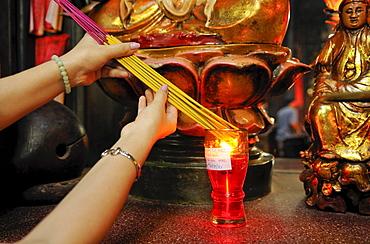 Igniting incense in Phuoc An Hoi Quan Pagoda, Ho Chi Minh City, Saigon, Vietnam, Southeast Asia