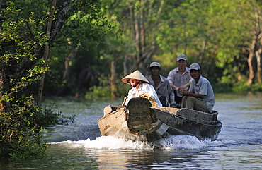 Woman wearing a traditional Vietnamese straw hat navigating a boat on the Mekong River, three men are seated behind her, Vinh Long, Mekong Delta, Vietnam, Asia