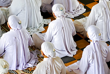 Nuns, ceremonial midday prayer in the Cao Dai temple, Tay Ninh, Vietnam, Asia