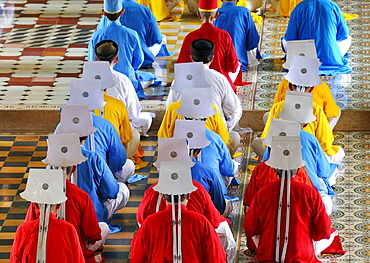 Monks and nuns, colorful robes in red, yellow, blue, praying, ceremonial midday prayer in the Cao Dai temple, Tay Ninh, Vietnam, Asia
