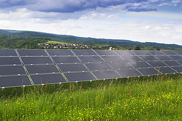 Solar power plant on a green field, photovoltaic system, view of a series of several modules