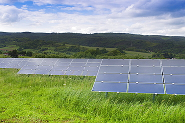 Photovoltaic, modules directed on different stands or racks on green meadow