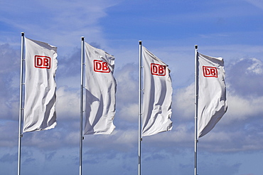 Four windblown white flags with the logo of DB, German Railways, in front of a sunny sky