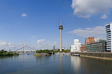 "Panoramic view, Duesseldorf Medienhafen media port, Neuer Zollhof with ""Dancing Office Buildings"" by F.O. Gehry, Rheinturm tower and Landtag parliament, Oberkasseler Bruecke bridge, in the front sport boats at the pier and water, Duesseldorf, state capita"