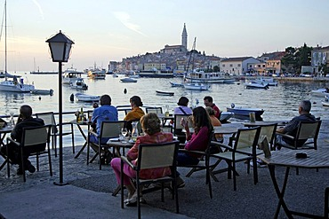 Cafe at sunset overlooking the Old Town and harbor, Rovinj, Istria, Croatia