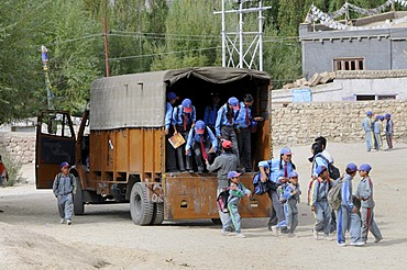 Schoolchildren in school uniform getting out of a truck that serves as a school bus, Secondary Senior School, Lamdon, Leh, Jammu and Kashmir, India, Himalayas, Asia