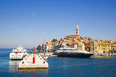The pier of the southern harbour with motor yacht Sibelle and catamaran against Rovinj historic centre, Istria, Croatia, Europe