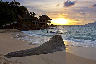 Typical granite rock of the Seychelles on the beach at dusk near Glacis, Sunset Beach Resort at back, island of Mahe, Seychelles, Indian Ocean, Africa