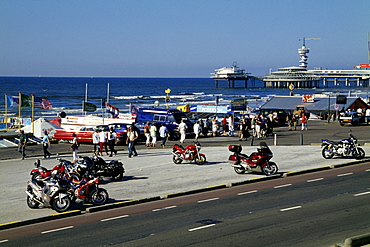 Motorcycles parked on the boulevard Strandweg, behind that the pier on the beach of Scheveningen, a chic seaside resort grown together with The Hague, Province of South Holland, Zuid-Holland, Netherlands, Benelux, Europe