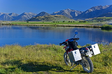 Enduro motorcycle in the morning light on the bank of Maori Lake, South Island, New Zealand