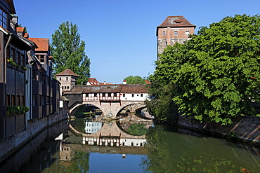 Executioner's home with half-timbered building, bridge building with two arches, small fortified tower and high water tower, Pegnitz river, trees, reflection, old town, Nuremberg, Middle Franconia, Franconia, Bavaria, Germany, Europe