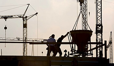 Construction workers working on a building site in front of a backdrop of several cranes in Waltrop, North Rhine-Westphalia, Germany, Europe