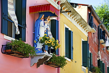 Madonna figure at the colorfully painted houses of Burano, Venice, Italy, Europe
