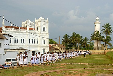 School girls in white school uniforms, in front of mosque and lighthouse, Fort Galle, Ceylon, Sri Lanka, South Asia, Asia