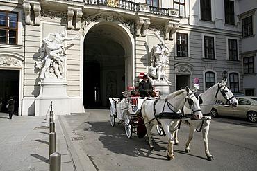 Fiaker, horse drawn carriage, entering the Heldenplatz, Heroe's Square through the Hofburg Castle, Vienna, Austria