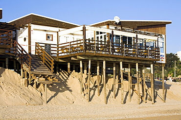 Soil erosion, beach bar on spiles nearly washed away by the sea in the sand by Algarve, Praia Alvor, Portugal, Europe
