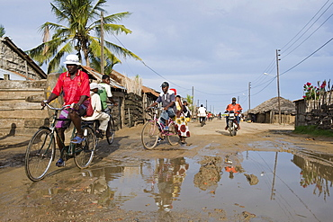 Road with water filled potholes provide breeding grounds for Malaria mosquitoes, Quelimane, Mozambique, Africa