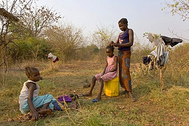 Mother dressing her daughter's hair, African village Sambona, Southern Province, Republic of Zambia, Africa