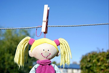 A child's soft toy hanging on washing line to dry after being washed