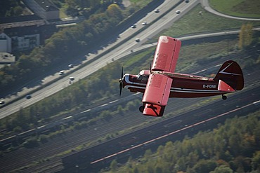 Aerial photograph, motorway, red double decker aircraft, oldtimer, veteran airplane, historical airplane, Antonow double decker AN-2 in flight over Bismarck, Gelsenkirchen, Ruhr Area, Germany, Europe